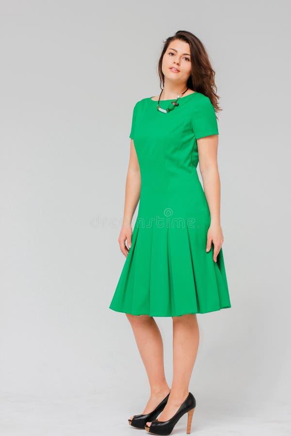 Ung charmig brunettkvinna med lockigt hår i elegant grön klänning royaltyfri fotografi
