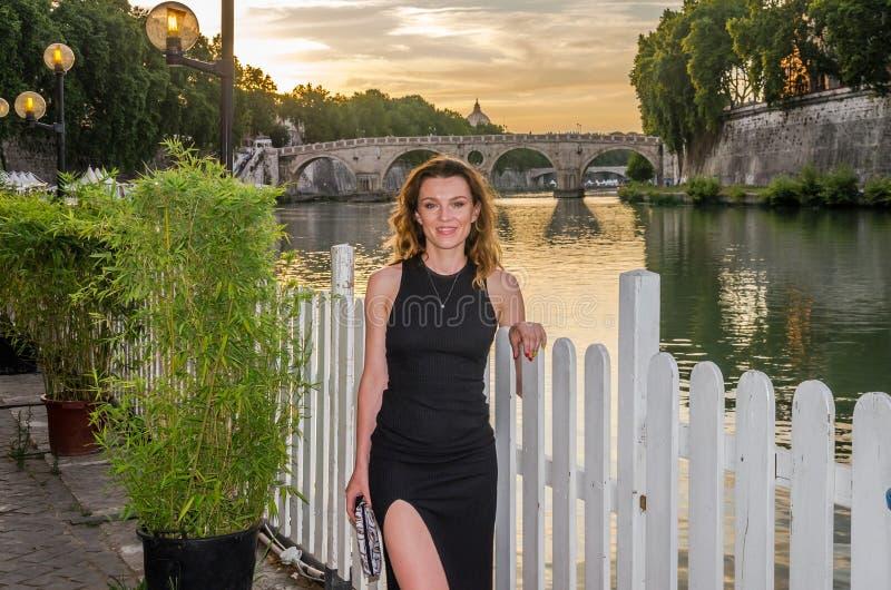 Ung charmig flicka i en klänning under en gå på solnedgången längs den Tiber flodinvallningen nära Vaticanen fotografering för bildbyråer
