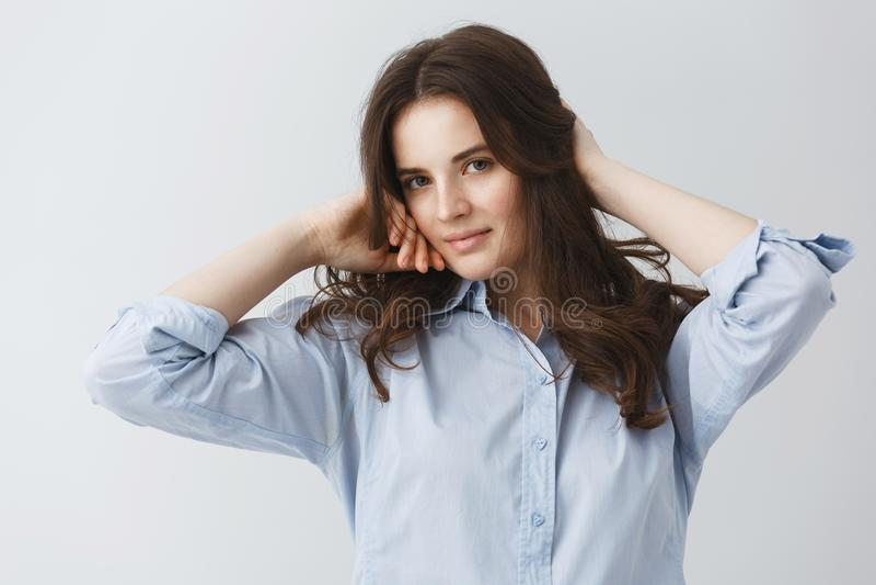 Ung charmig flicka med härligt mörkt hår i blåa skjortainnehavhänder i hår som in camera ser med mjukt och försiktigt arkivfoton