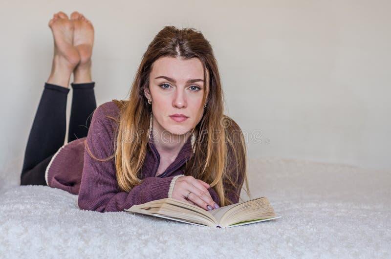 Ung charmig flickastudent med långt hår som ligger på sängen som läser en bok och förbereder sig för grupper royaltyfri bild