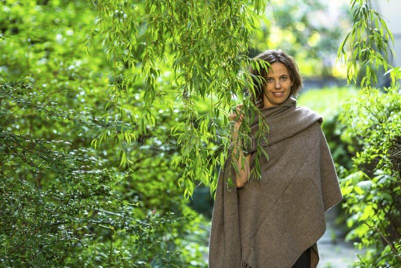 Ung charmig kvinna i parkera bland de gröna träden Gå arkivfoto