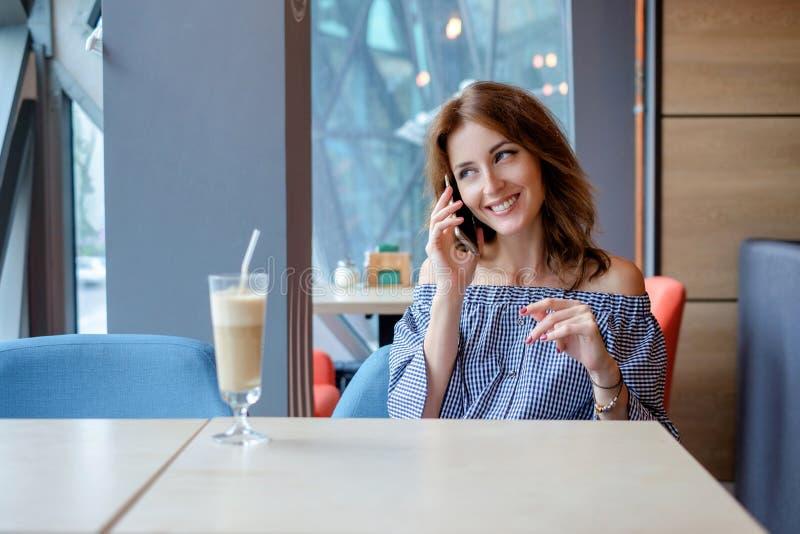 Ung charmig kvinna som kallar med celltelefonen, medan sitta bara i coffee shop, attraktiv kvinnlig med gulligt leende arkivbild