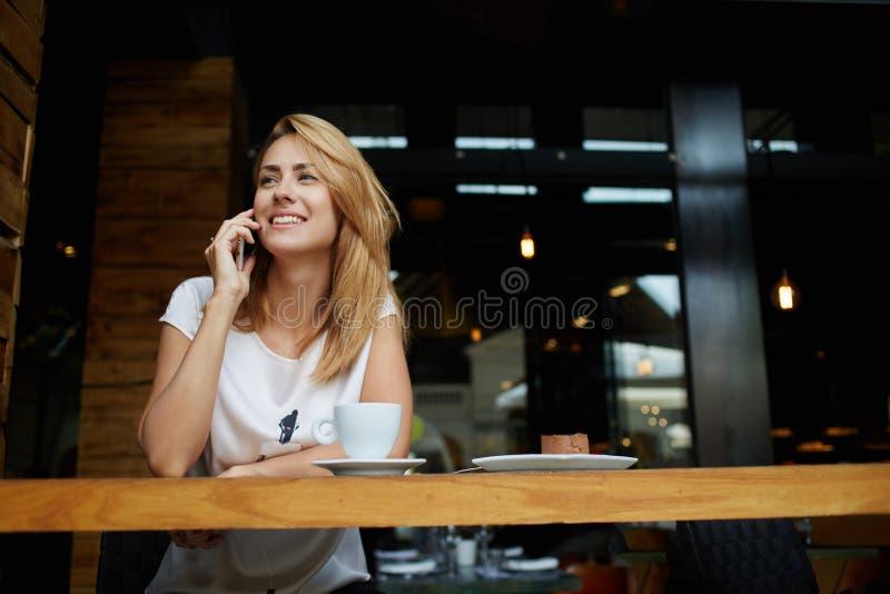 Ung charmig kvinna som kallar med celltelefonen, medan sitta bara i coffee shop under fri tid, arkivbild