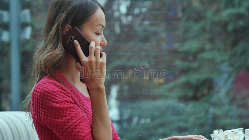 Ung charmig kvinna som kallar med celltelefonen, medan sitta bara i coffee shop under fri tid arkivfoto
