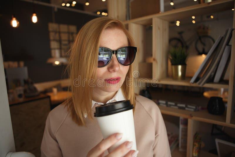 Ung charmig kvinna som kallar med celltelefonen, medan sitta bara i coffee shop under fri tid, attraktiv kvinnlig arkivfoto