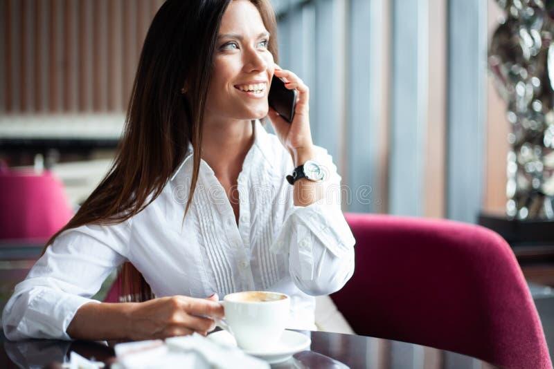 Ung charmig kvinna som kallar med smartphonen, medan sitta bara i coffee shop under fri tid, attraktiv kvinnlig med fotografering för bildbyråer