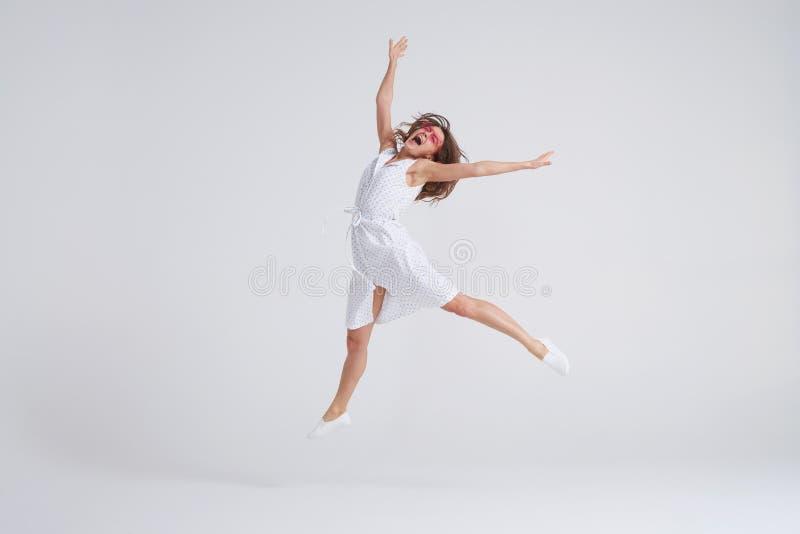 Ung charmig kvinnlig i klänning som hoppar över vit bakgrund royaltyfria foton