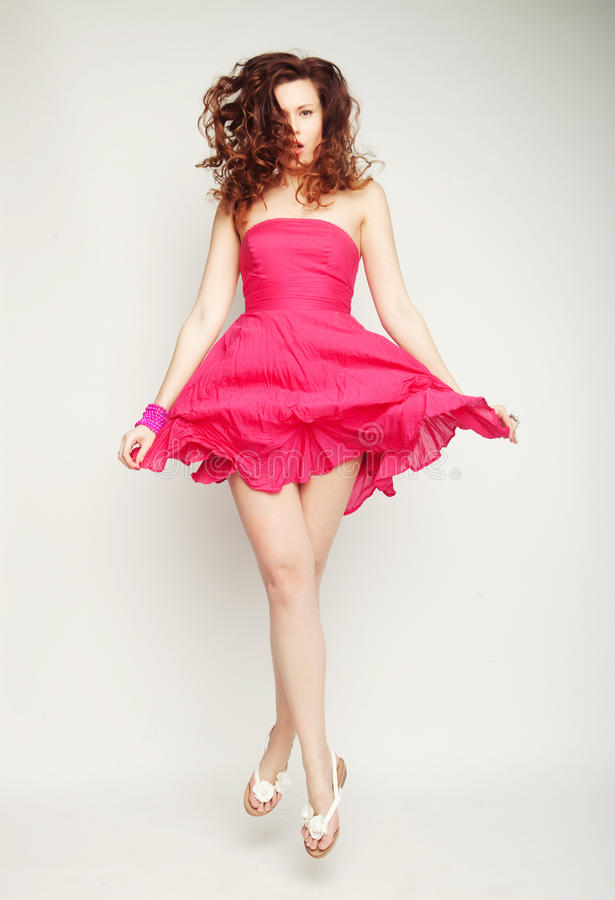 Ung charmig kvinnlig i rosa färgklänningbanhoppning arkivfoton