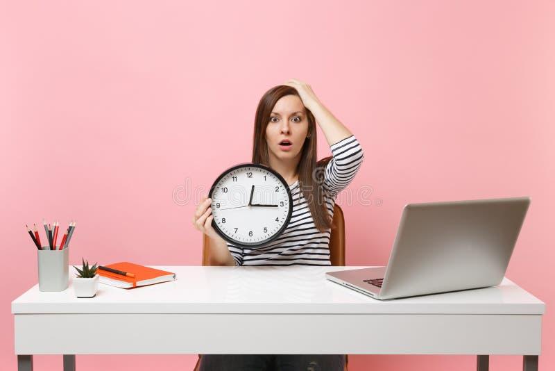 Ung chockad kvinna som klamra sig fast intill huvudhållringklockan, medan sitt arbete på kontoret med den isolerade PCbärbara dat royaltyfri fotografi
