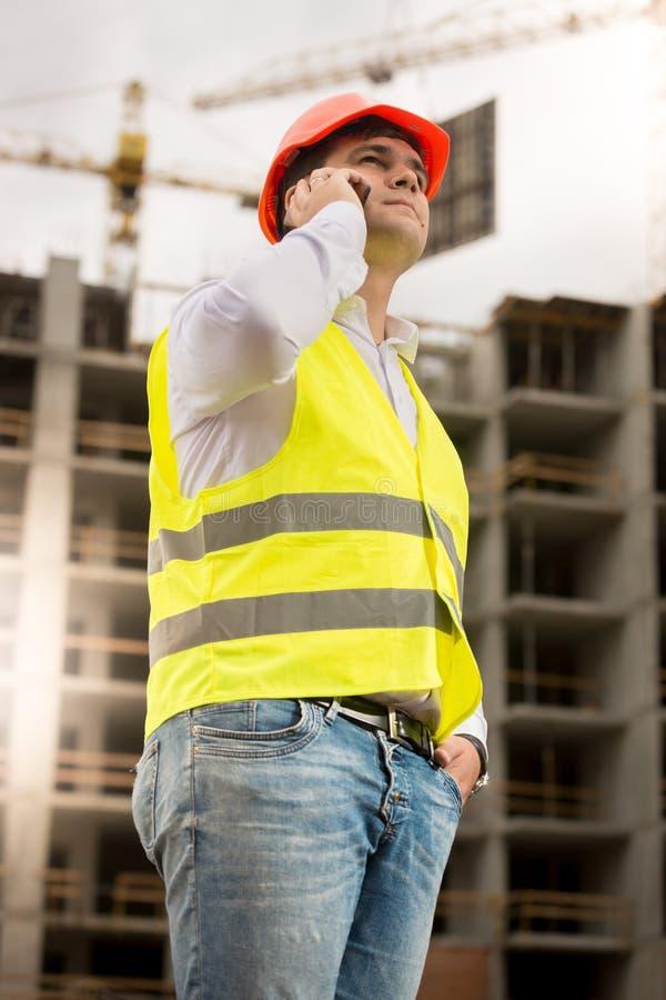Ung construcitontekniker i hardhat som talar vid telefonen mot byggnad under konstruktion royaltyfri foto
