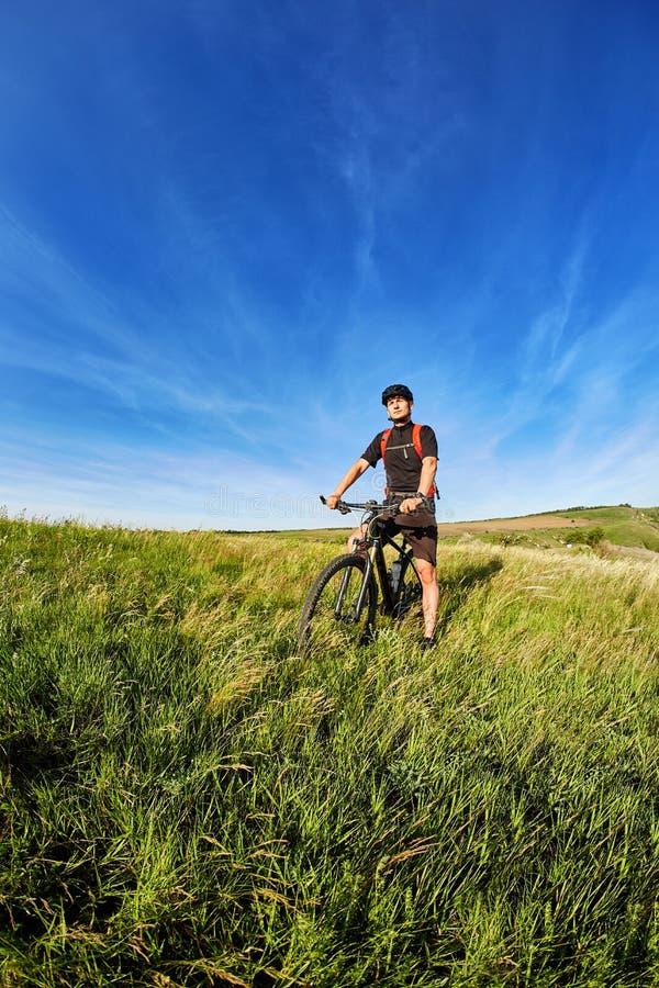 Ung cyklist som cyklar på den gröna ängen mot härlig blå himmel med moln i bygden arkivfoton