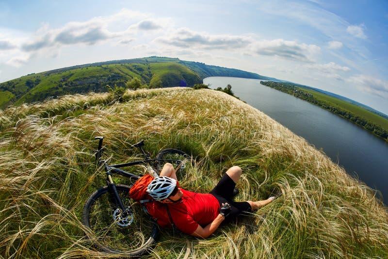 Ung cyklist som vilar på ängen på reverside i berg med bergcykeln mot härlig himmel arkivfoton