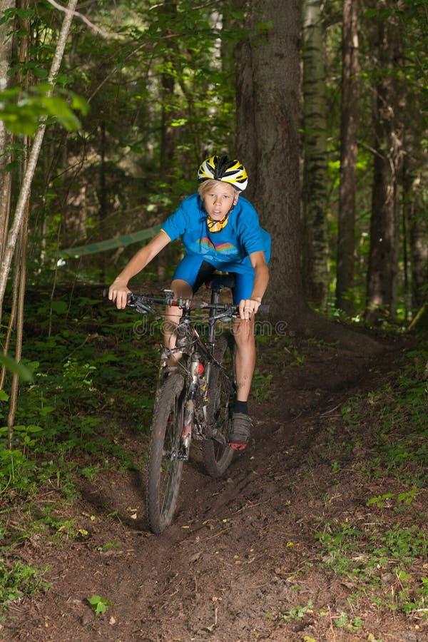 Ung cyklistridning i skog royaltyfri fotografi