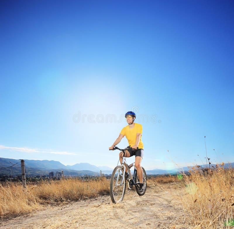 Ung cyklistridningmountainbike i ett fält royaltyfri fotografi
