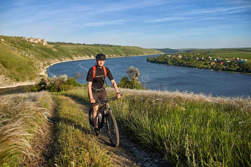 Ung cyklistridningmountainbike som är stigande längs en landsväg ovanför floden arkivfoton