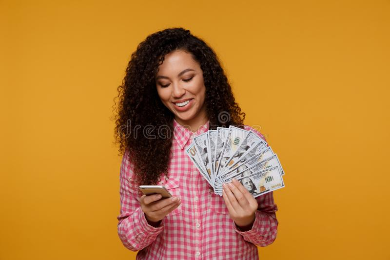 Ung dam över blå bakgrund Se kameravisningskärm av hållande pengar för mobiltelefon arkivfoto