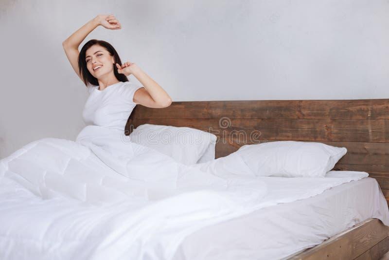 Ung dam av övernaturlig skönhet som sträcker armar på säng arkivfoton