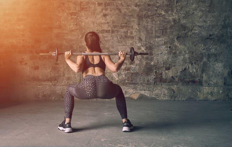 Ung dam i den svarta sportswearen som gör squats med skivstången Styrka- och motivationbegrepp arkivfoton
