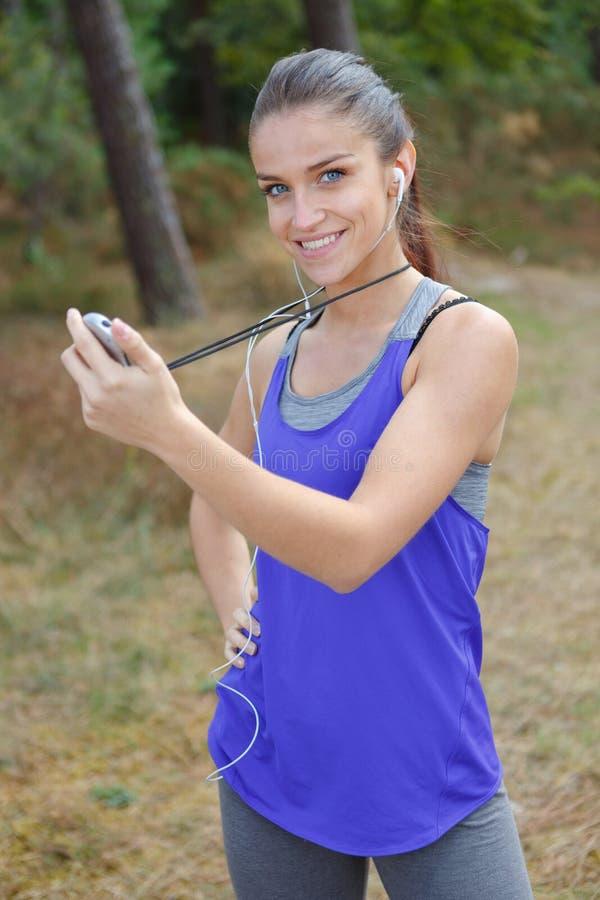 Ung dam i hållande stoppur för sportswear royaltyfria foton
