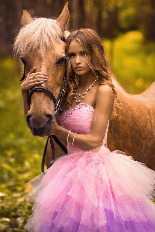 Ung dam i skogen med hennes häst arkivfoto