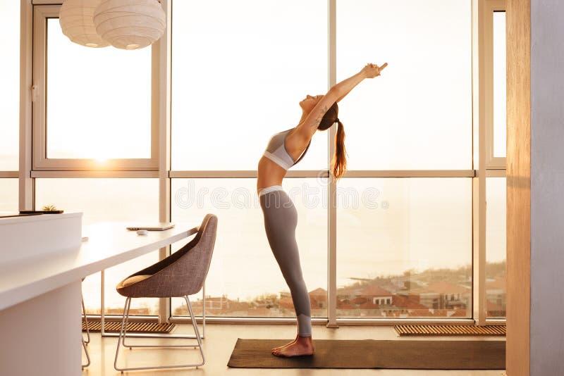Ung dam i sportig överkant och damasker som hemma står övande yoga över härligt fönster arkivbild