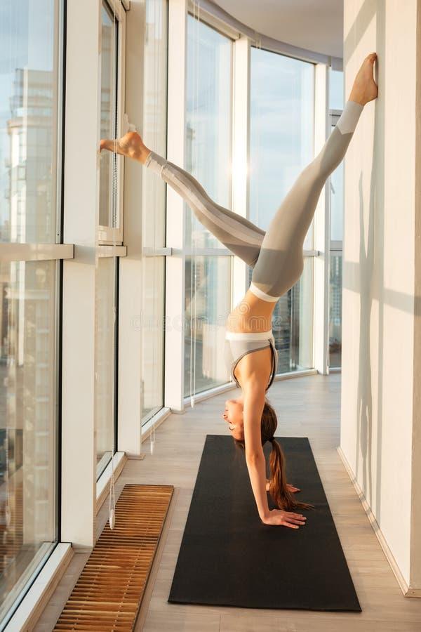 Ung dam i sportig överkant och damasker som står på händer som öva yoga på yoga som är matt med stadssikt arkivbild