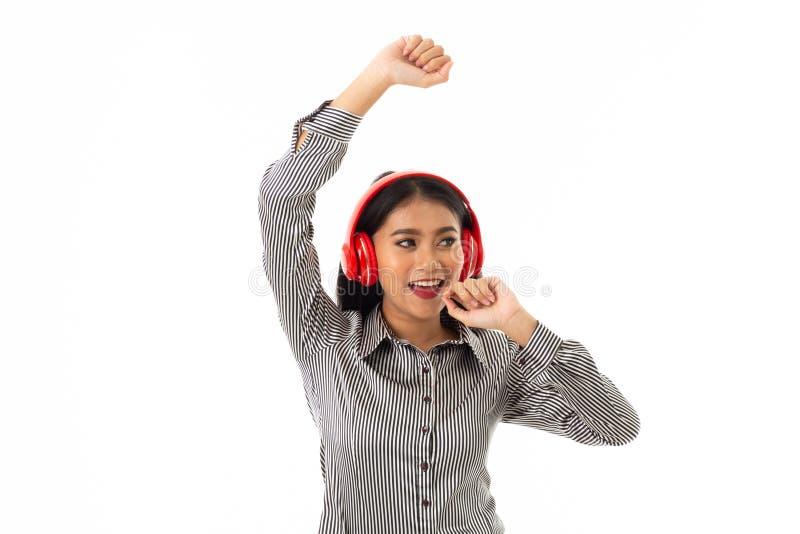 Ung dam med röd hörlurar som ser på vänster handside arkivbilder