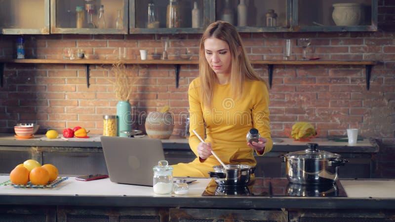 Ung dam som använder datoren och lagar mat lunch royaltyfri fotografi