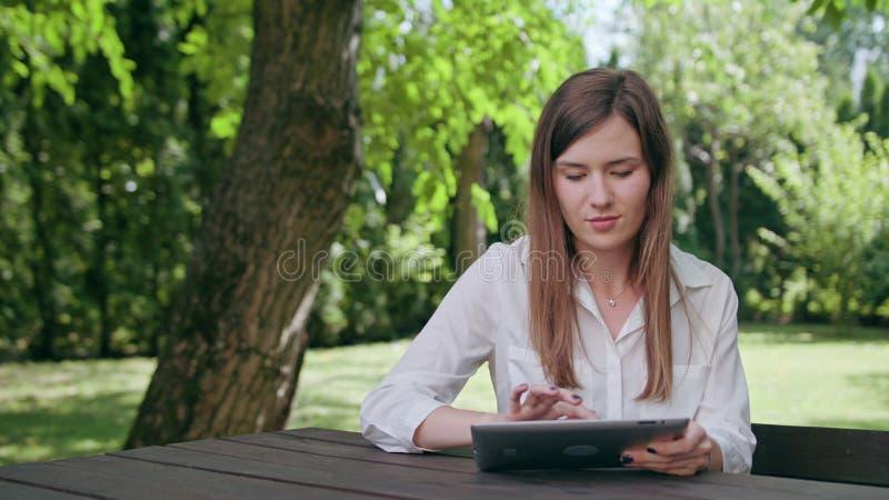 Ung dam som använder en ipad i parkera arkivfoton