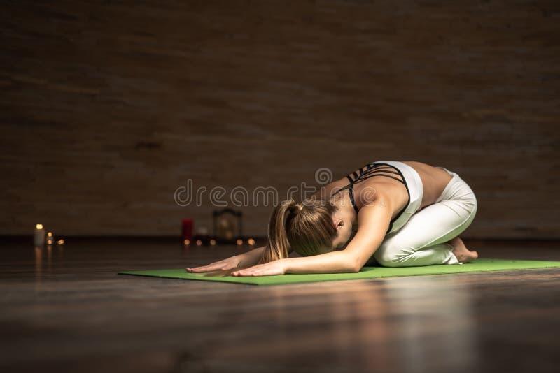 Ung dam som böjer hennes baksida, medan öva yogaasanas arkivfoton