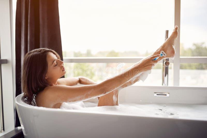 Ung dam som rakar hennes ben i badet royaltyfria foton