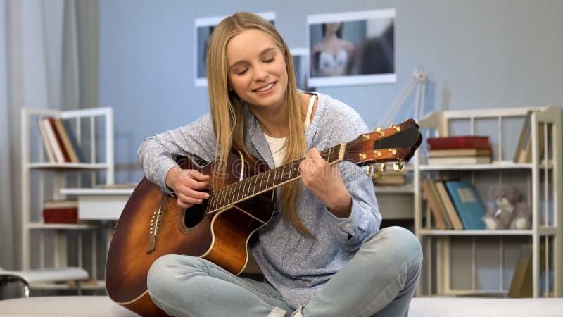 Ung dam som spelar gitarren i hennes rum och att skriva sången som drömmer av musikkarriär royaltyfri foto