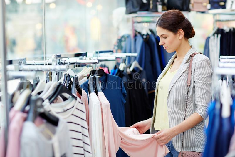 Ung dam som väljer kläder i lager fotografering för bildbyråer