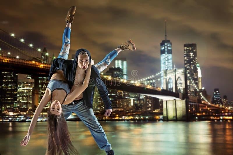 Ung dans för höftflygturpar, över stads- bakgrund arkivfoto