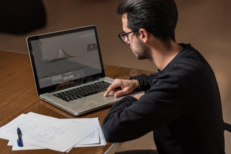 Ung datavetenskapstudent att använda en bärbar dator för att studera i Caceres, Spanien arkivfoto