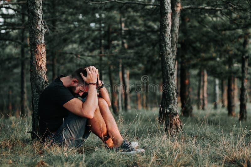 Ung deprimerad man som bara sitter i träna royaltyfri fotografi