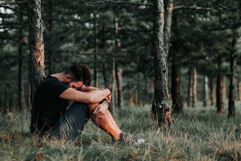 Ung deprimerad man som bara sitter i träna arkivbilder