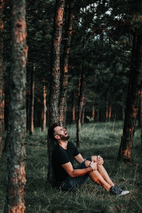 Ung deprimerad man som bara sitter i träna royaltyfri foto