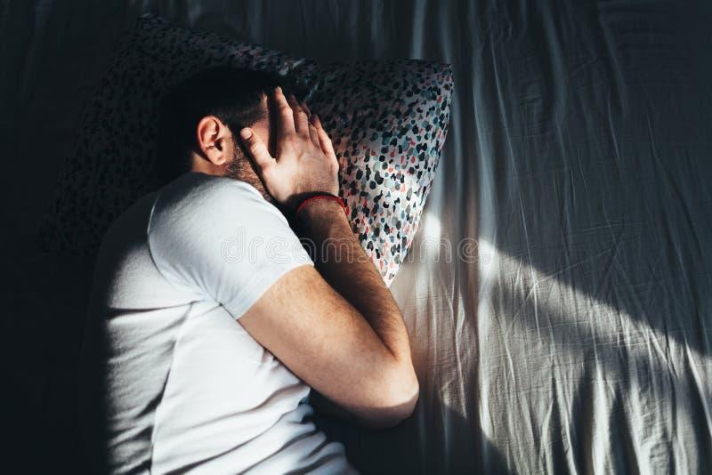 Ung deprimerad man som gråter i säng royaltyfria foton