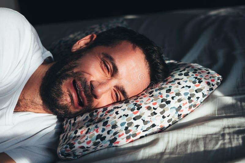 Ung deprimerad man som gråter i säng royaltyfri bild