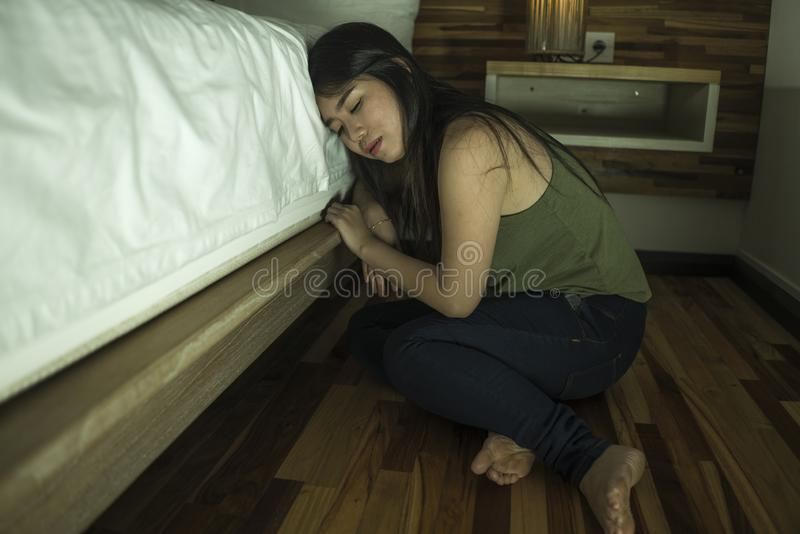 Ung deprimerad och ledsen asiatisk koreansk kvinna som sitter på golv på sovrummet bredvid säng som lider fördjupningsproblem och arkivbild