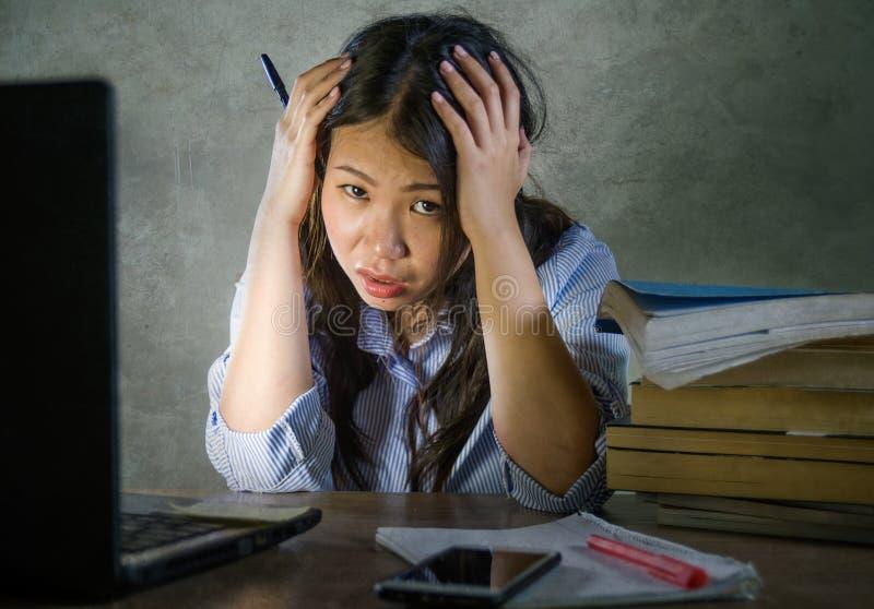 Ung deprimerad och stressad asiatisk kinesisk studentflicka som arbetar med bärbar dator- och bokhögen som förkrossas och den fru arkivfoton