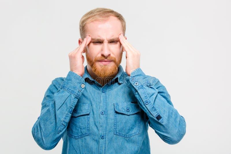 Ung deprimerad skäggig man som trycker på hans tempel och har huvudvärk arkivfoton