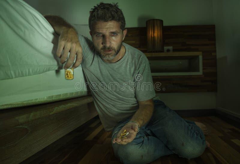 Ung desperat och deprimerad ensam man som sitter på sovrumgolvet som gråter det sjuka lida fördjupningsproblemet som tar pillerkä royaltyfria bilder