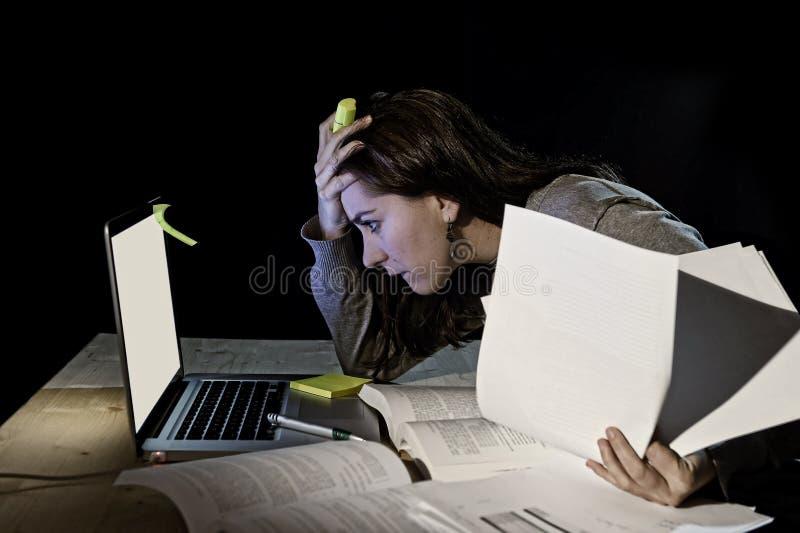 Ung desperat universitetsstudentflicka i spänningen för examen som sent studerar med böcker och datorbärbara datorn på natten royaltyfria bilder