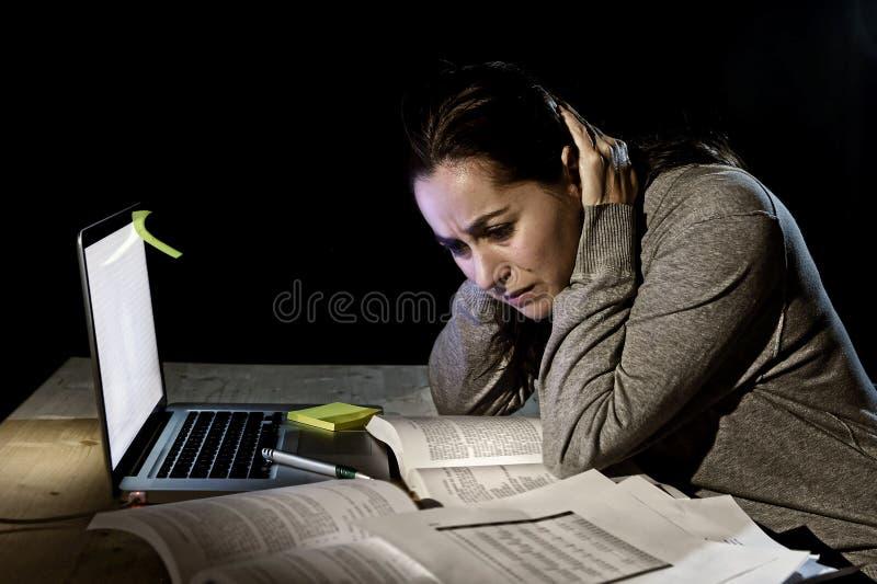 Ung desperat universitetsstudentflicka i spänningen för examen som sent studerar med böcker och datorbärbara datorn på natten arkivbild