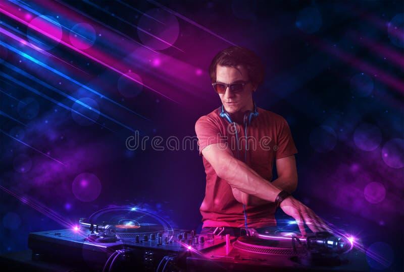 Ung discjockey som spelar på skivtallrikar med ljusa effekter för färg arkivbilder