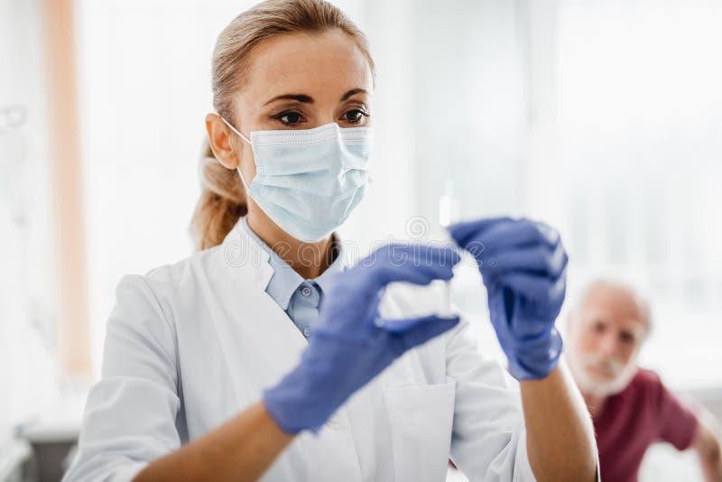 Ung doktor i den skyddande maskeringen som förbereder sig att göra injektionen arkivbilder