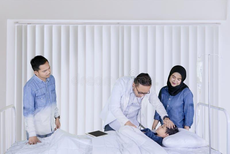 Ung doktor som lite undersöker pojken i kliniken royaltyfri fotografi