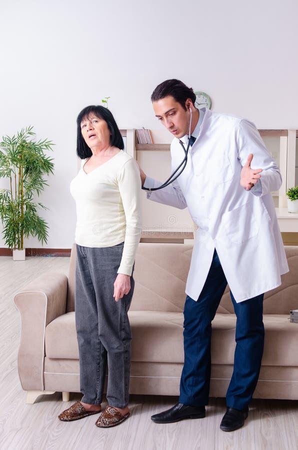 Ung doktor som undersöker den höga gamla kvinnan arkivfoto